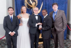five people dressed in formally holding an Emmy award