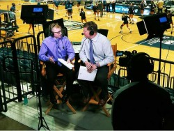 two reporters sitting in the bleachers conducting an interview in front of a basketball game