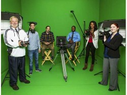 six professionals standing in front of a green screen holding video equipment